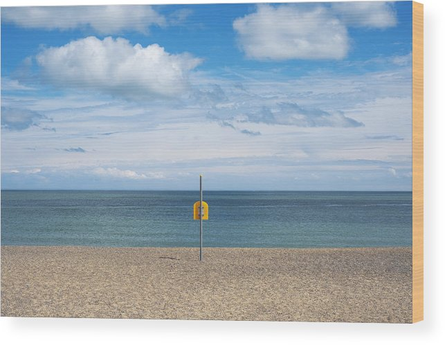 Tranquility Wood Print featuring the photograph Life Bouy on empty beach on Irelands East Coast by Catherine MacBride