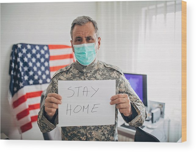 Working Wood Print featuring the photograph Senior military soldier holding paper with message stay home by Hirurg