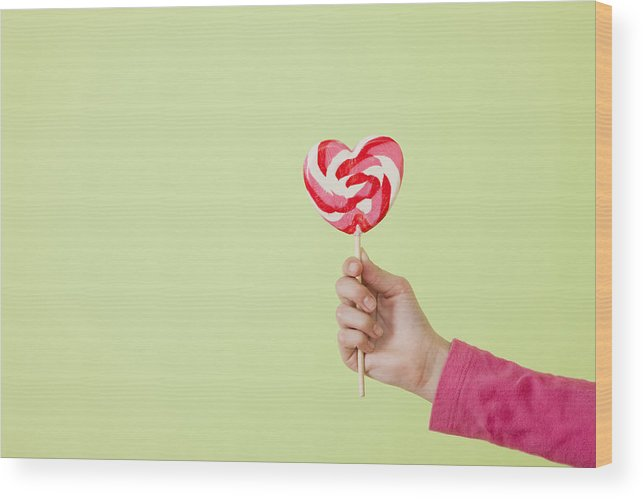 Child Wood Print featuring the photograph Studio shot of girl's (10-11) hand holding heart-shaped lollipop by Vstock LLC