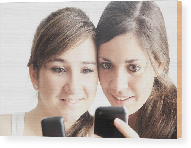 People Wood Print featuring the photograph Teenage girls using cell phones by Sigrid Gombert