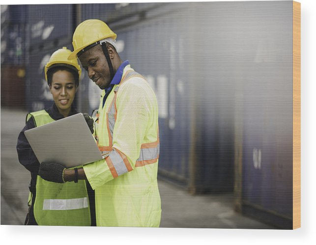 Working Wood Print featuring the photograph Young African american men and woman worker Check and control loading freight Containers by use computer laptop at commercial shipping dock felling happy. Cargo freight ship import export concept by Niphon Khiawprommas