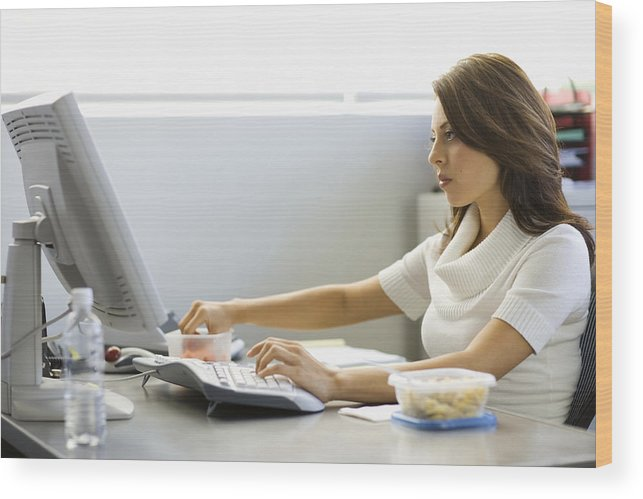 Sweater Wood Print featuring the photograph Young businesswoman eating lunch at desk by Siri Stafford