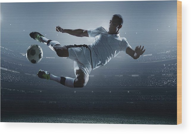 Goal Wood Print featuring the photograph Soccer Player Kicking Ball In Stadium by Dmytro Aksonov