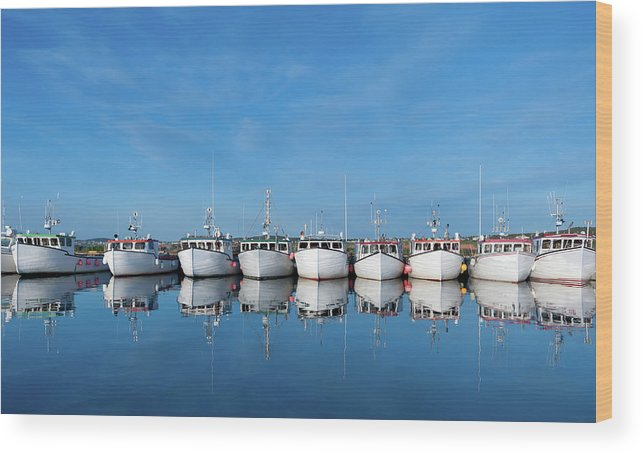 Iles De La Madeleine Wood Print featuring the photograph Row Of Boats With Reflection by Pndtphoto