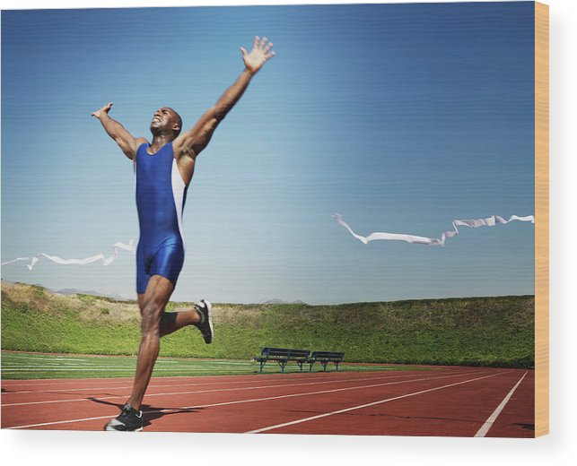 Human Arm Wood Print featuring the photograph Runner Crossing Finish Line by Jupiterimages