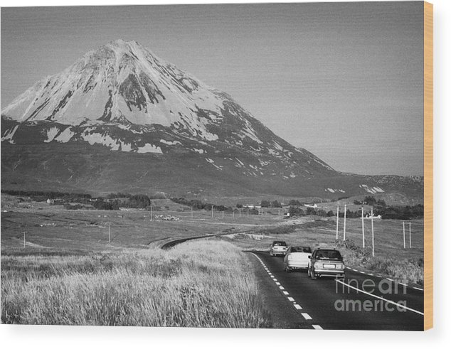 County Wood Print featuring the photograph cars in the evening on the road towards Errigal mountain donegals highest peak against a blue sky between dunlewey and gweedore white quartzite conical cone county Donegal Republic of Ireland by Joe Fox