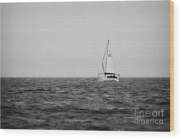 Ireland Wood Print featuring the photograph lone yacht off Rathlin Island against grey sky with sea County Antrim Northern Ireland by Joe Fox