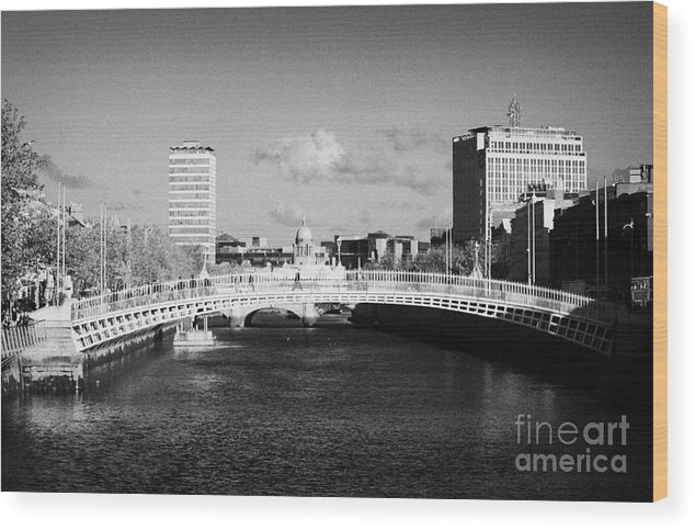 Dublin Wood Print featuring the photograph Looking Down The Liffey Towards The Hapenny Ha Penny Bridge Over The River Liffey In Dublin by Joe Fox