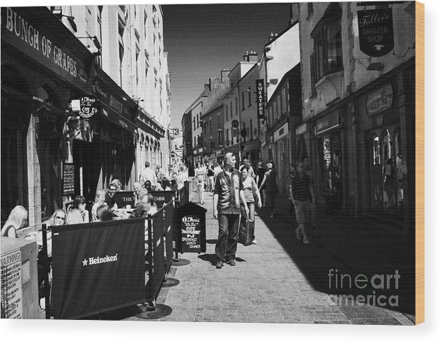 Galway Wood Print featuring the photograph pedestrians and drinkers enjoying a sunday afternoon drink in the bunch of grapes pub high street Ga by Joe Fox