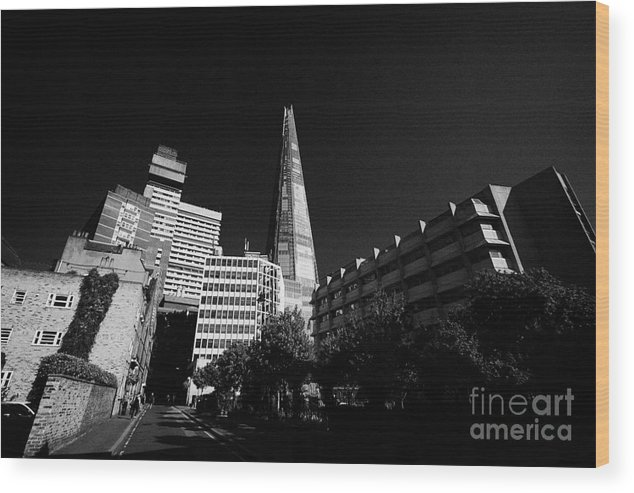 Shard Wood Print featuring the photograph the shard building towering over local buildings including guys hospital in southwark London England by Joe Fox