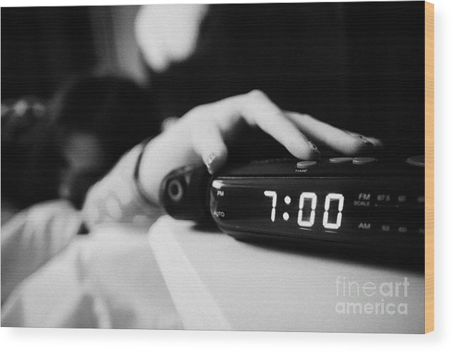 Alarm Clock Early Morning With Early Twenties Woman Turning Off Alarm Lying  In Bed In A Bedroom Wood Print