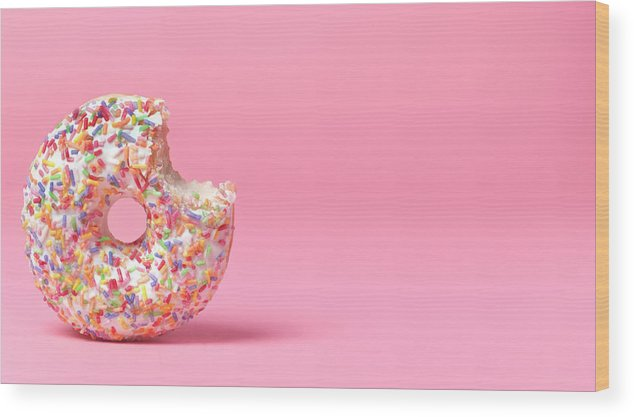 Unhealthy Eating Wood Print featuring the photograph Doughnut On Pink With Bite Out by Peter Dazeley