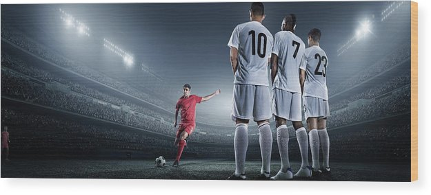 Soccer Uniform Wood Print featuring the photograph Soccer Player Kicking Ball In Stadium by Dmytro Aksonov