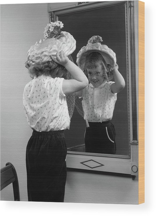 Photography Wood Print featuring the photograph 1950s Little Girl Trying On Hat Looking by Vintage Images