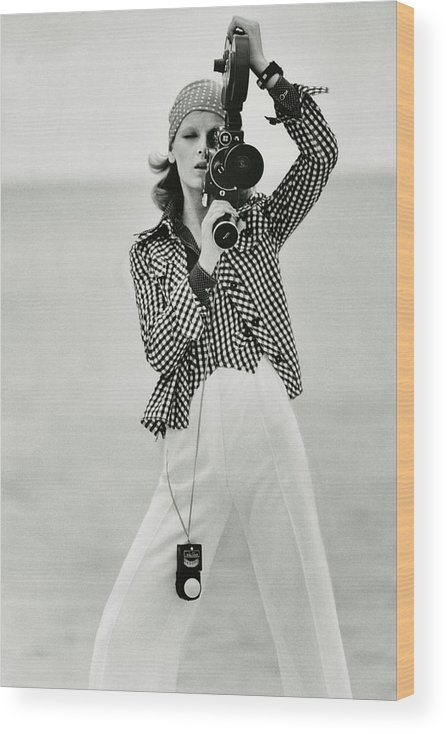 Fashion Wood Print featuring the photograph A Model Looking Through A Beaulieu Camera Wearing by Gianni Penati