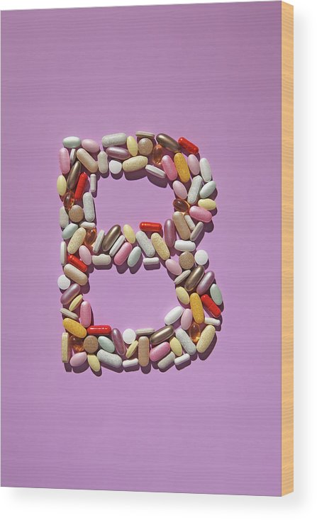 Vitamin Wood Print featuring the photograph Multi-vitamin Pills And Capsules by Nicholas Eveleigh