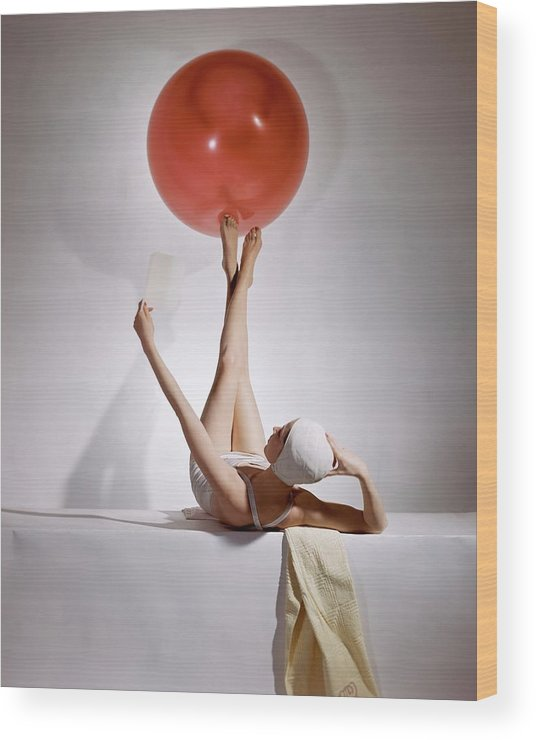 Fashion Wood Print featuring the photograph A Model Balancing A Red Ball On Her Feet by Horst P Horst