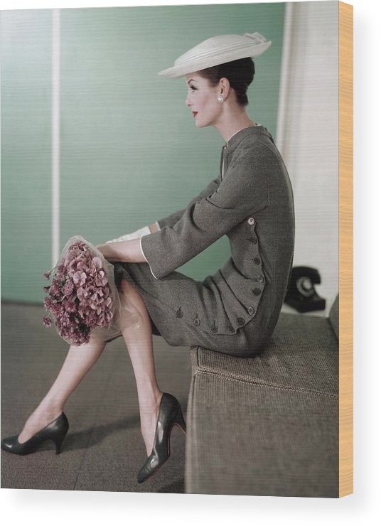 Fashion Wood Print featuring the photograph A Model Sitting Down With A Bouquet Of Flowers by Karen Radkai