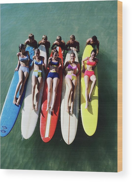 Fashion Wood Print featuring the photograph Models Wearing Bikinis Lying On Surfboards by William Connors