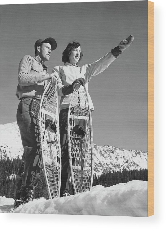 Heterosexual Couple Wood Print featuring the photograph Couple Holding Snowshoes, Woman Pointing by Stockbyte