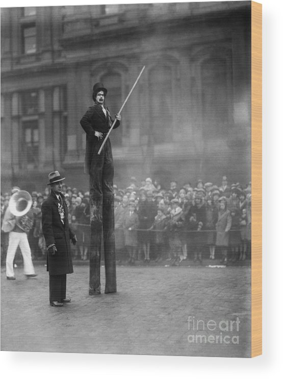 Crowd Of People Wood Print featuring the photograph Performer On Stilts by Bettmann