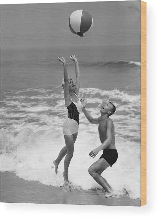 Young Men Wood Print featuring the photograph Young Couple Playing With Beach Ball At by Stockbyte