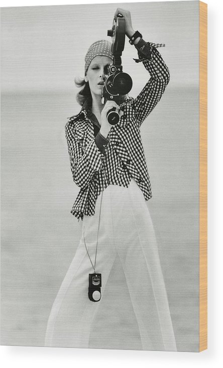 Fashion Wood Print featuring the photograph A Model Looking Through A Beaulieu Camera Wearing by Gianni Penati