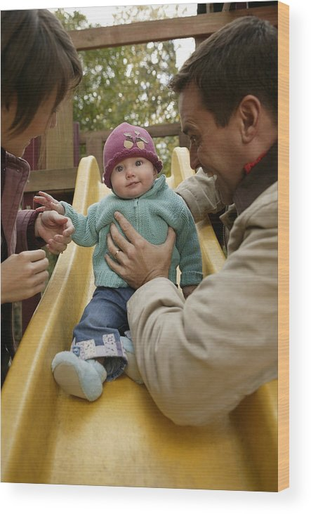 Mid Adult Women Wood Print featuring the photograph Parents With Baby Playing On Slide by Comstock Images