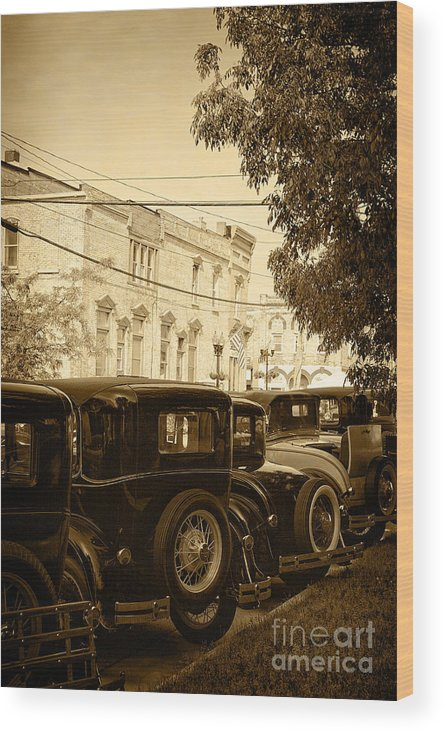 Model A; Vintage; Antique; Buildings; Wires; Trees; Street; City; Town; Parked; Back; Tires; Flags; Lights; Electricity; Sepia; Cars; Autos; Automobiles; Transportation; Turn Of The Century; Early 1900s; 20s; 1920s; Ford; Road; Vehicle Wood Print featuring the photograph Parked Model A's by Margie Hurwich