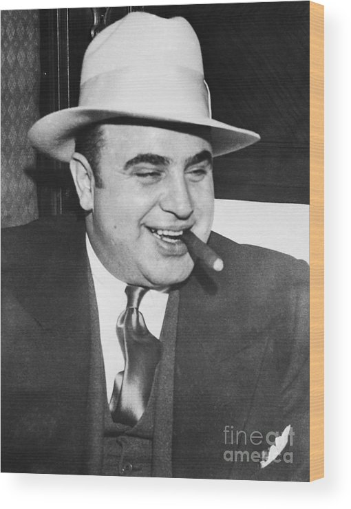 Al Capone Wood Print featuring the photograph Gangster Al Capone Smoking Cigar by Bettmann