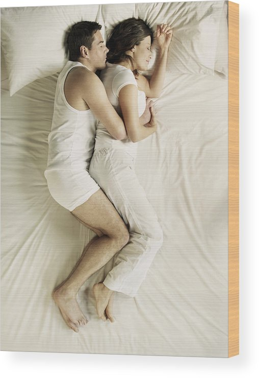 Heterosexual Couple Wood Print featuring the photograph Man and woman cuddling in bed by Flashpop
