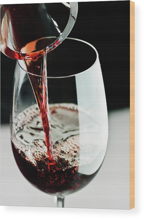 Alcohol Wood Print featuring the photograph Red Wine Being Poured In A Glass by Juanmonino