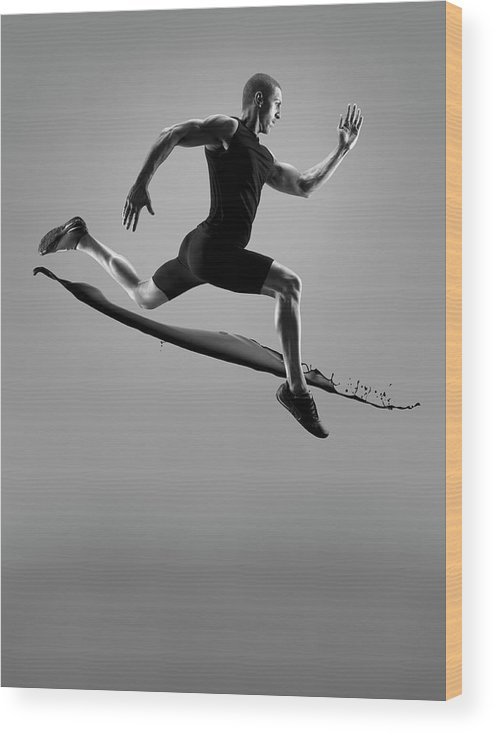 People Wood Print featuring the photograph Male Athlete Running Above Liquid Splash by Jonathan Knowles