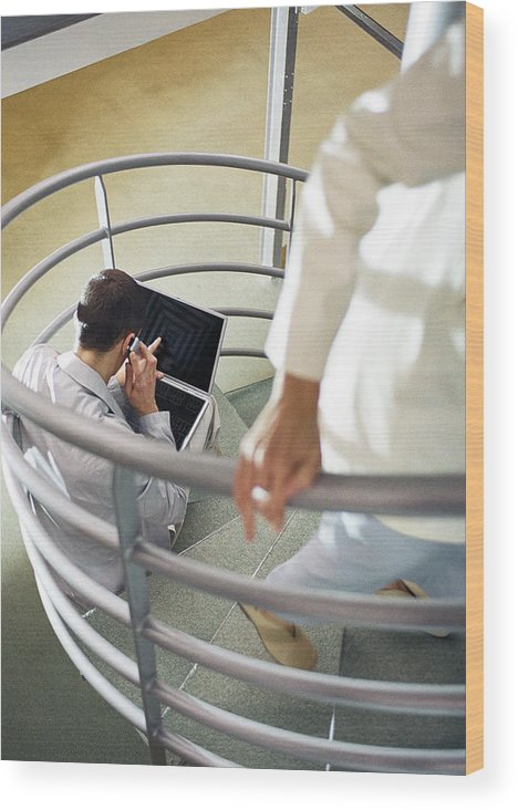 New Business Wood Print featuring the photograph Focus on man sitting on stairs with cell phone and laptop computer, person walking up stairs in foreground, blurred. by Coco Marlet