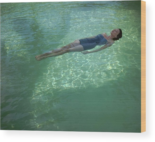 Exterior Wood Print featuring the photograph A Model Floating In A Swimming Pool by John Rawlings