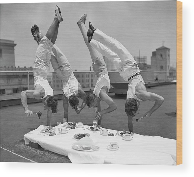 People Wood Print featuring the photograph Acrobats Eat While Doing Handstands by Bettmann