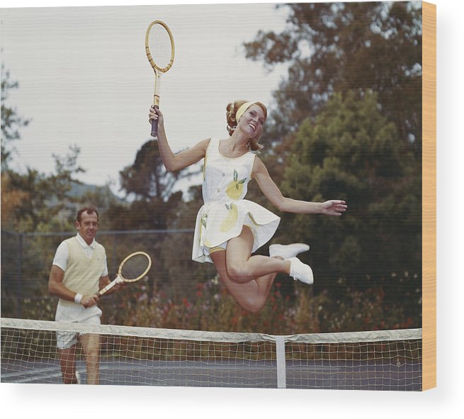 Heterosexual Couple Wood Print featuring the photograph Couple On Tennis Court, Woman Jumping by Tom Kelley Archive