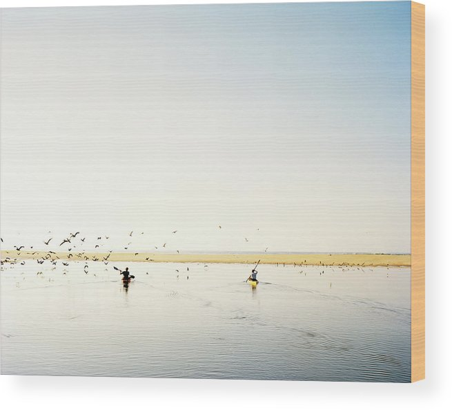 People Wood Print featuring the photograph Men Paddling Kayaks To The Beach by Julien Capmeil