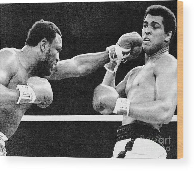 Joe Frazier Wood Print featuring the photograph Joe Frazier Throwing Punch At Muhammad by Bettmann