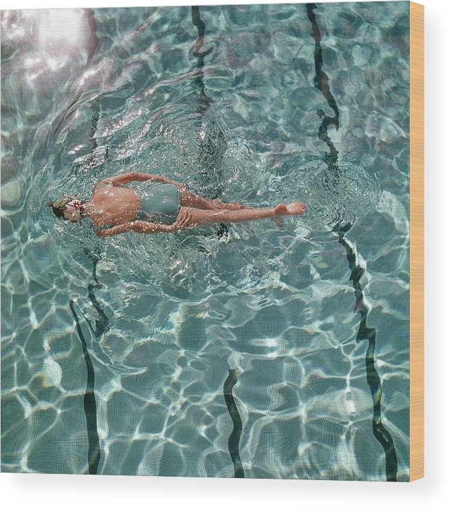 Water Wood Print featuring the photograph A Woman Swimming In A Pool by Fred Lyon