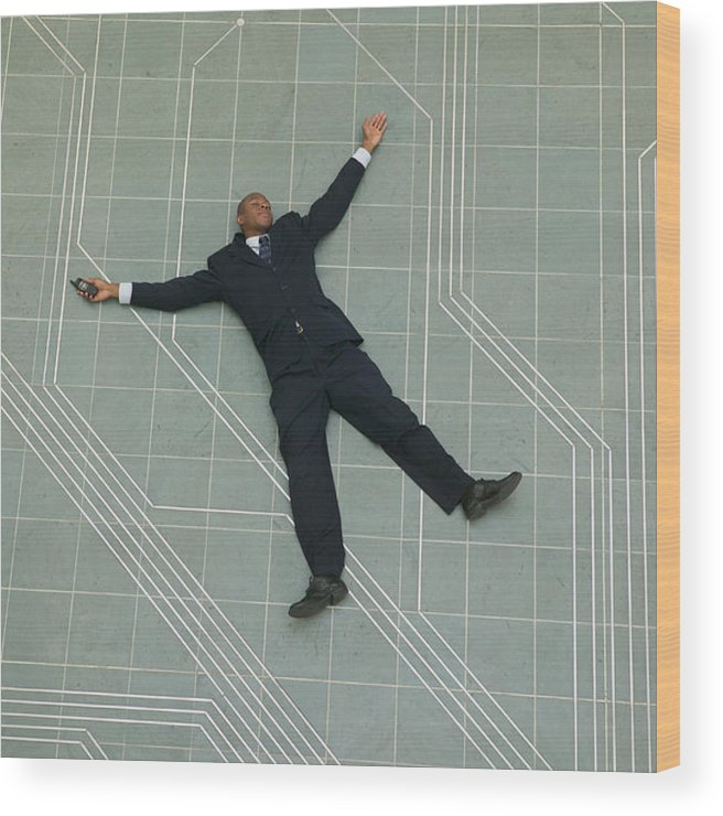Corporate Business Wood Print featuring the photograph Conceptual Shot Of An African American Business Man As He Lays Flat On The Ground Holding His Phone by Photodisc