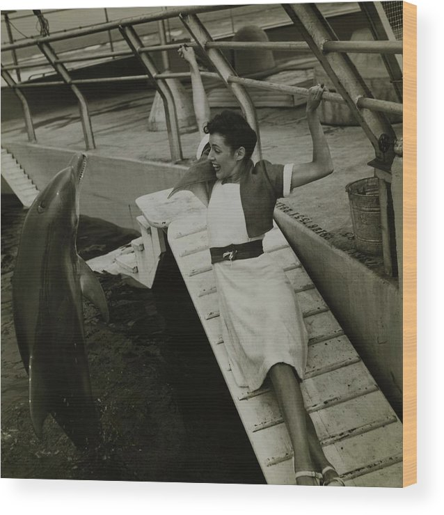 Accessories Wood Print featuring the photograph Model Wearing A Cannon Outfit By A Dolphin by Toni Frissell