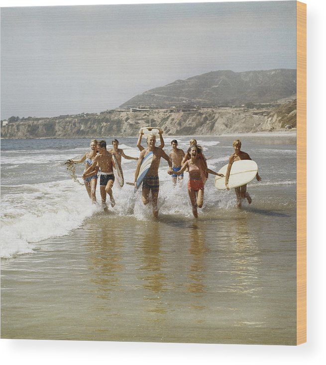 Young Men Wood Print featuring the photograph Group Of Surfers Running In Water With by Tom Kelley Archive