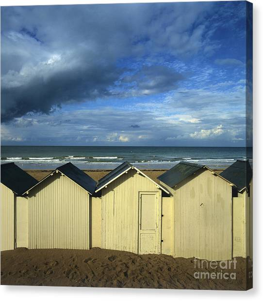 Beach Cabin Canvas Print - Beach Huts Under A Stormy Sky In Normandy. France. Europe by Bernard Jaubert