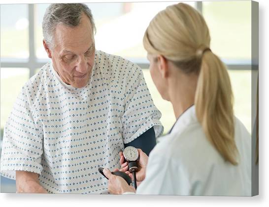 Female Doctor Taking Senior Man's Blood Pressure Canvas Print by Science Photo Library