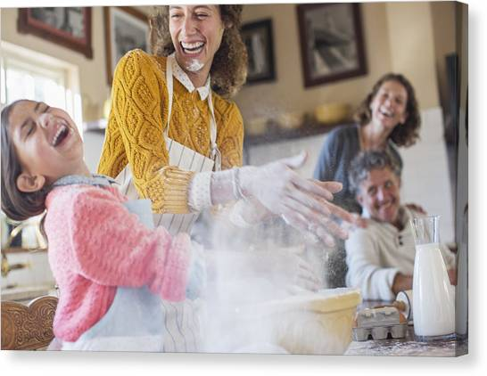 Mother And Daughter Playing With Flour In The Kitchen Canvas Print by Caiaimage/Sam Edwards