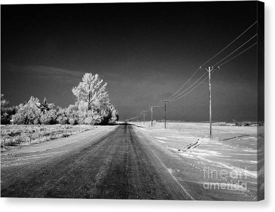 Harsh Conditions Canvas Print - salt and grit covered rural small road in Forget Saskatchewan Canada by Joe Fox