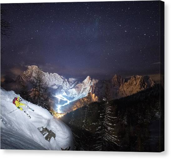 Skier Riding Down A Powder Slope At Night Canvas Print by Leander Nardin
