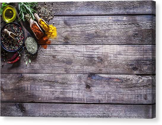 Spices And Herbs On Rustic Wood Kitchen Table Canvas Print by Fcafotodigital