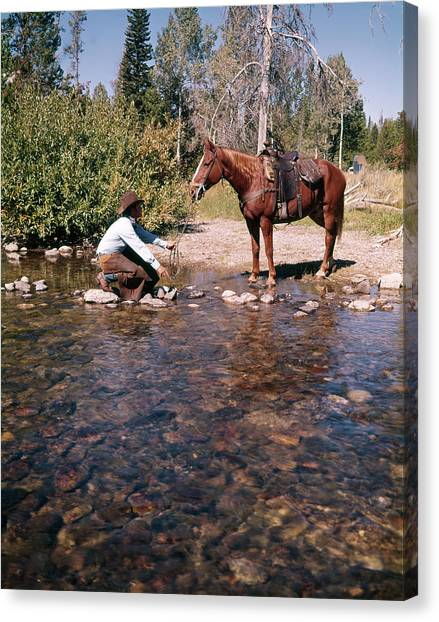 Lead Character Canvas Print - 1970s Cowboy In Stream Kneeling Try by Vintage Images